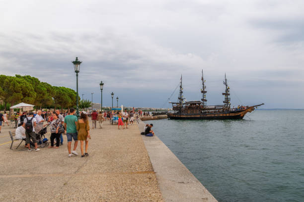 Thessaloniki, Greece - August 15 2019: Tourist ship moored by the waterfront while crowd passes by. A ship with tourists, moored at Thermaikos gulf seafront before White Tower, the city landmark. stock photo
