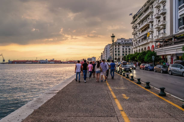 Thessaloniki, Greece - August 15 2019: Unidentified crowd at the historic waterfront. People walk along the promenade towards the city port during golden hour with passing cars at Nikis Avenue. stock photo