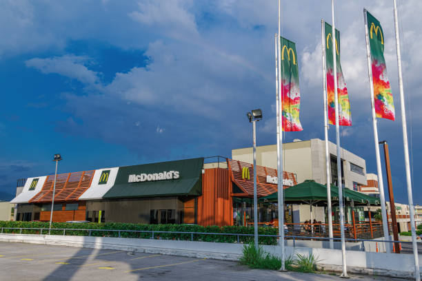 Thessaloniki, Greece - June 25 2019: McDonalds store facade new design. External day view of international fast-food chain with famous yellow arch company logo and waving flags. stock photo
