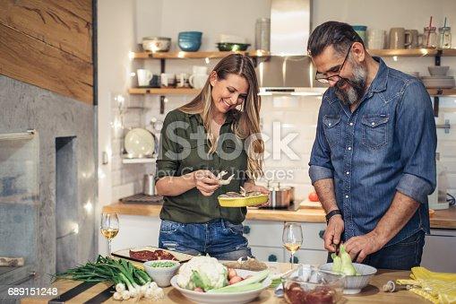 Happy couple preparing dinner at modern kitchen.