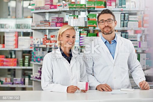 Shot of two pharmacists working in a drugstore. All products have been altered to be void of copyright infringements