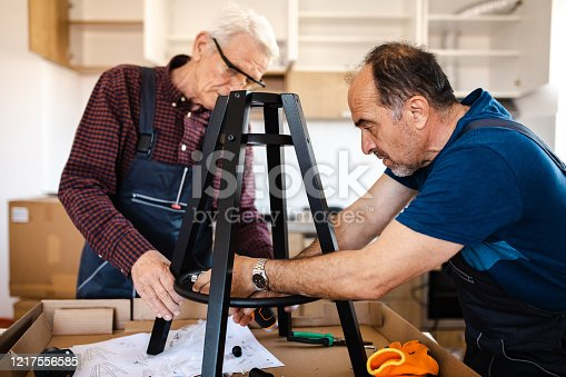 Dedicated senior manual workers working in client's house on montage of new furniture