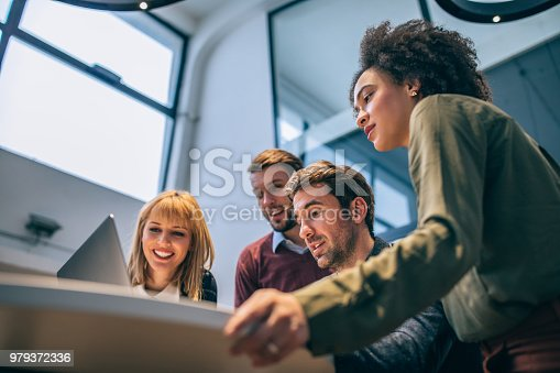Low angle shot of coworkers looking at a laptop computer