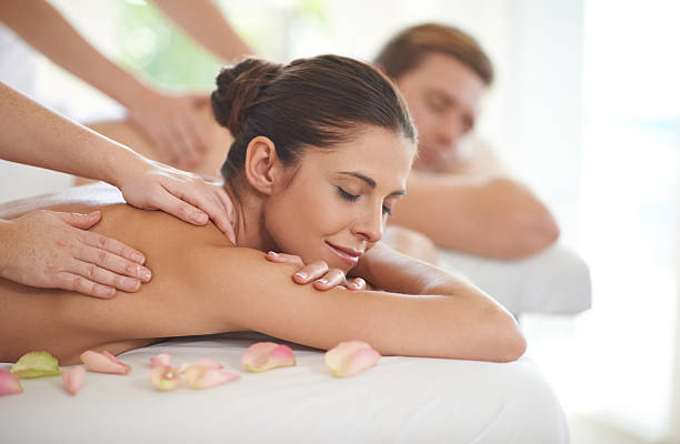 They deserve this pampering A husband and wife lying receiving massages at a spa massaging stock pictures, royalty-free photos & images