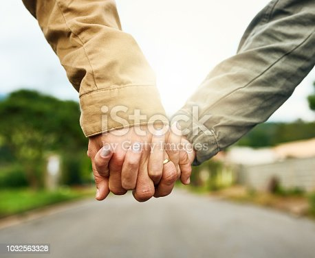 Cropped shot of an unrecognizable couple holding hands outdoors