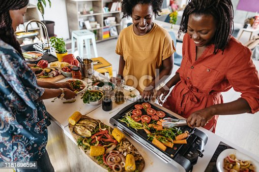Group of female friends making vegetarian lunch in the kitchen at apartment together