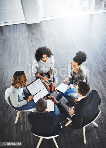 High angle shot of a group of businesspeople having a discussion in an office