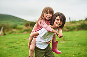 Portrait of a little boy giving his sister a piggyback ride outdoors