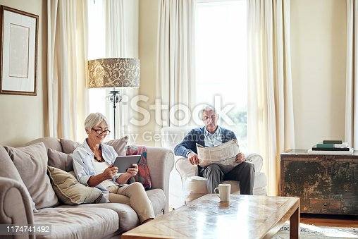 Shot of a senior woman using a digital tablet while her husband reads a newspaper at home