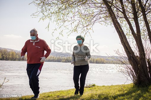 They keep each other moving. Senor couple at the nature with face mask.