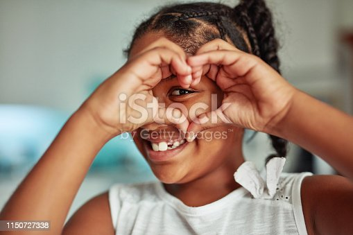 Cropped shot of a young girl forming a heart shape with her hands