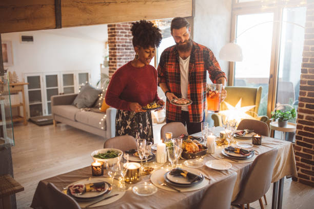 they love to participate in table preparation - new year day stock photos and pictures