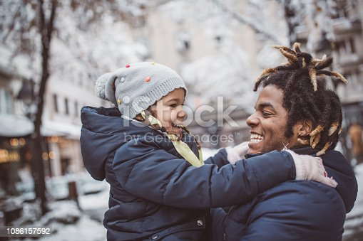 Young father with daughter walking on snowy street and enjoy in winter magic. They wearing warm clothing
