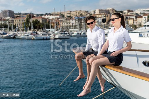 Horizontal color image of two people - fashion models/friends sitting on ship's bow of luxury yacht in port and looking at Mediterranean sea view. Focus on happy young couple having fun and wearing matching outfits and sunglasses, port in background.