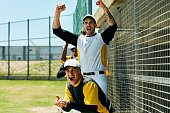 Cropped shot of a group of young baseball players cheering while standing near a baseball field during the day