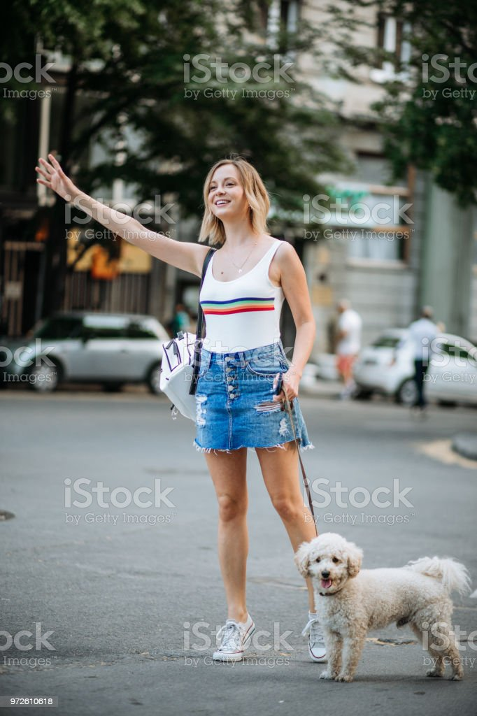Young woman with her dog try to catch taxi
