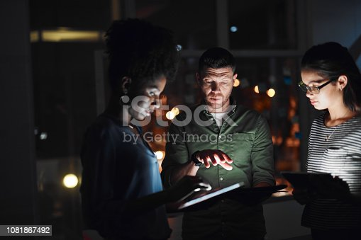 Shot of a group of businesspeople working together on a digital tablet in an office at night