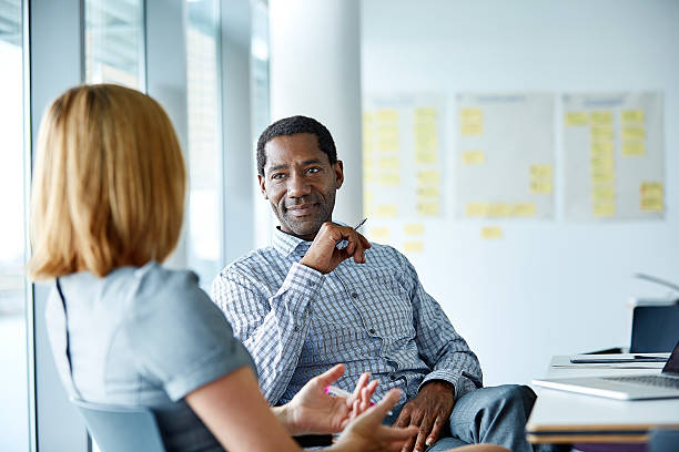 They share a great working relationship Shot of two colleagues talking together while sitting in a modern office two people stock pictures, royalty-free photos & images