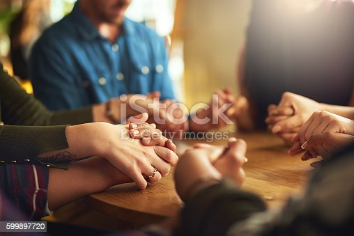 Shot of a group of people holding hands and praying together