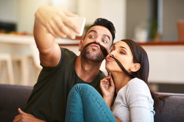 They share many light-hearted moments together Shot of a young couple taking selfies together at home mustache stock pictures, royalty-free photos & images