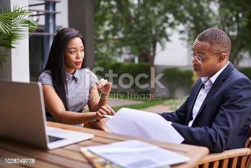 Shot of a young businesswoman and businessman discussing paperwork together outdoors