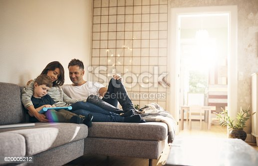 Shot of a little boy and his parents using a digital tablet together at home