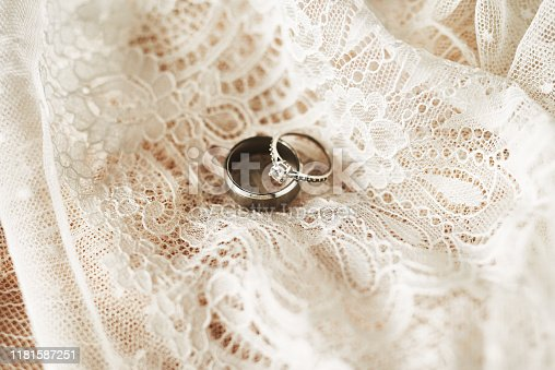 Still life shot of two beautiful wedding rings on top of a wedding dress