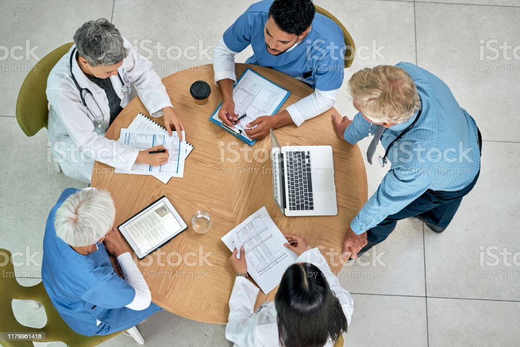 They take a multidisciplinary approach to healthcare High angle shot of a group of medical practitioners having a meeting in a hospital Adult Stock Photo