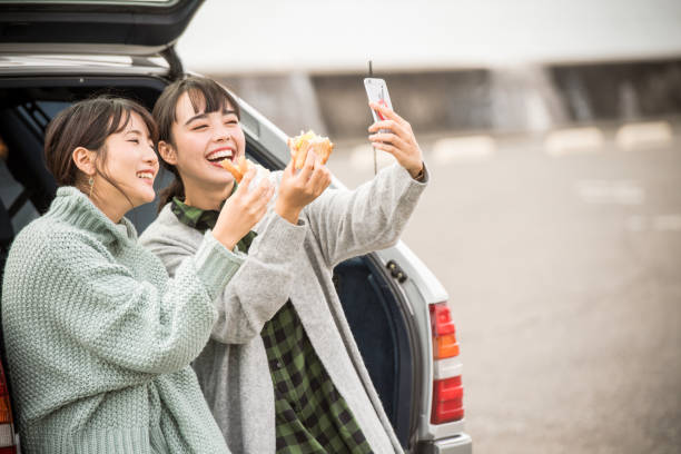 they take a sandwich lunch at the beachfront parking lot. . - asian travel in car stock photos and pictures