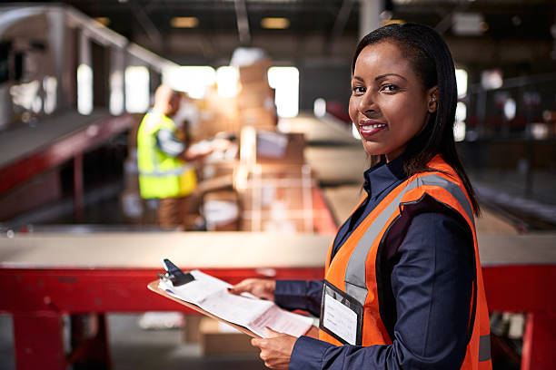 They take the headache out of shipping Portrait of a warehouse manager holding a clipboard with workers in the background foreman stock pictures, royalty-free photos & images