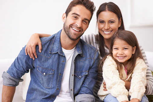 Portrait of a happy young family sitting together at home