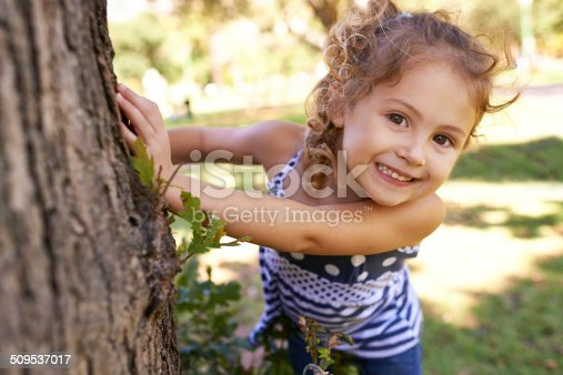 Portrait of a little girl hiding behind a tree in a park