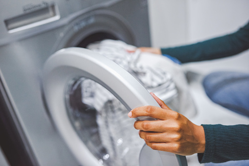Closeup shot of an unrecognisable woman using a washing machine to do laundry at home