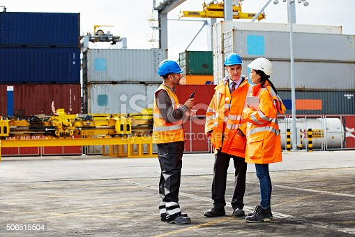 Shot of three workers talking together while standing on a commercial dock