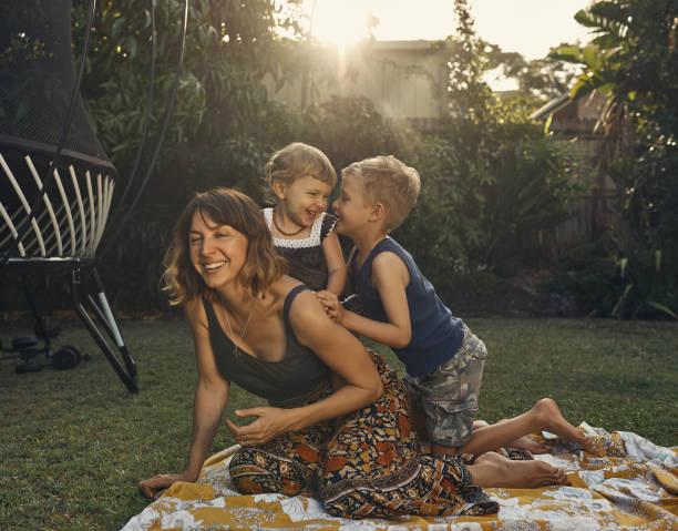 they're a close knit family - mãe criança brincar relva efeito de refração de luz imagens e fotografias de stock