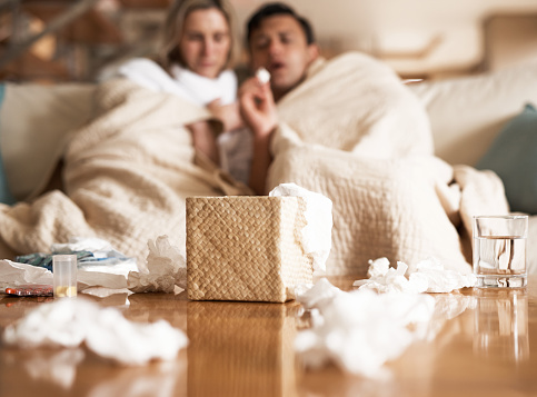 Cropped shot of an unrecognizable couple suffering with flu while sitting wrapped in blankets on the sofa at home