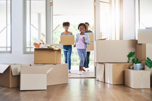 They're all excited about the big move Shot of a happy family carrying boxes into their new home physical activity stock pictures, royalty-free photos & images