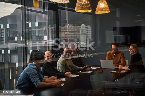 Cropped shot of a diverse group of businesspeople sitting and having a meeting in a boardroom while in the office