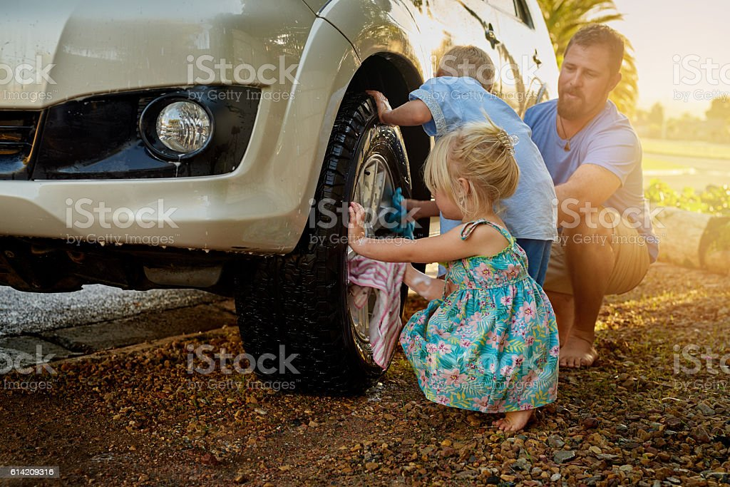 They're always eager to help Dad wash the car stock photo