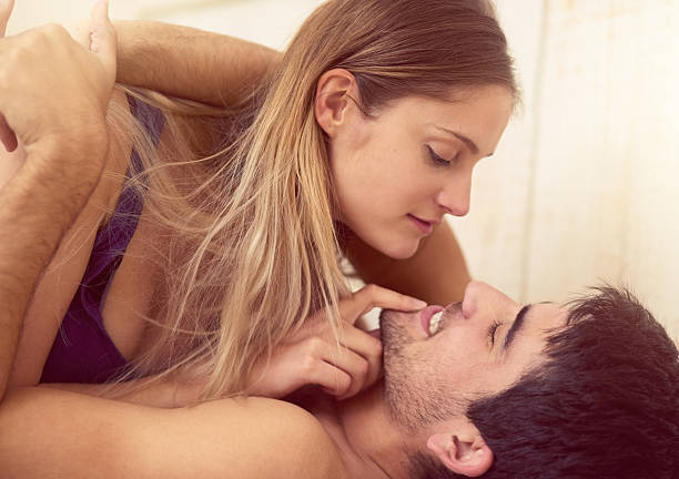 They're completely comfortable with each other Shot of a loving young couple getting intimate in bed real couples making love stock pictures, royalty-free photos & images