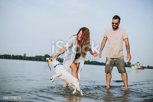 The young couple set on the banks of the river or the sea with his dog, jumping, running, laughing, in love with the play and are very happy