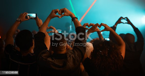 Rearview shot of unrecognizable people making heart shapes during a concert  in a nightclub