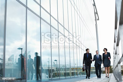 Shot of three businesspeople walking and talking next to an office building