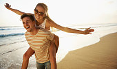 A young man piggybacking his girlfriend playfully on the beach