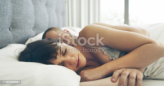 Cropped shot of an affectionate young couple sleeping together in their bed at home