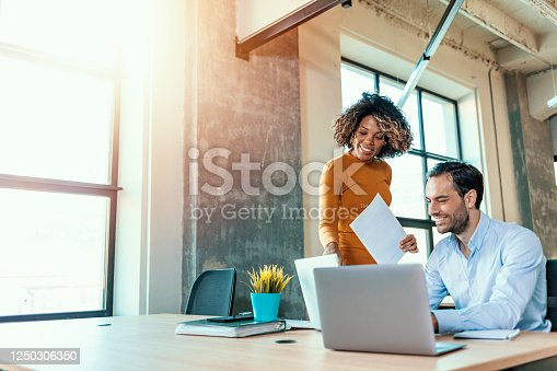 We already have great results! Young beautiful woman working, discussing something with her coworker while standing at office.