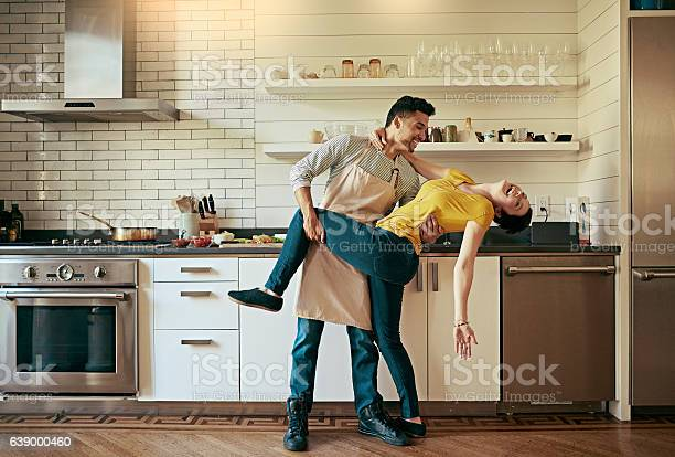 Shot of a young couple dancing in their kitchen