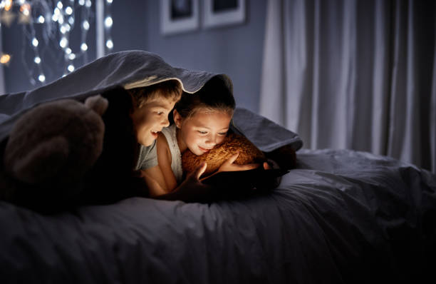 They're too entertained to sleep Shot of two adorable little siblings using a digital tablet together in bed at night girl bedroom stock pictures, royalty-free photos & images