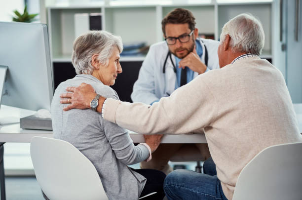 They're trying to remain positive despite their circumstances Shot of a senior man consoling his wife during a consultation with a doctor in a clinic despite stock pictures, royalty-free photos & images