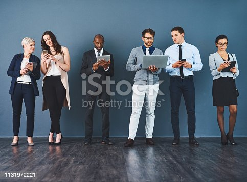 Studio shot of a group of businesspeople using various digital devices against a grey background
